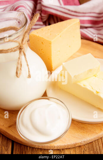 Dairy products - milk, cheese, butter, sour cream over wooden table - Stock Image