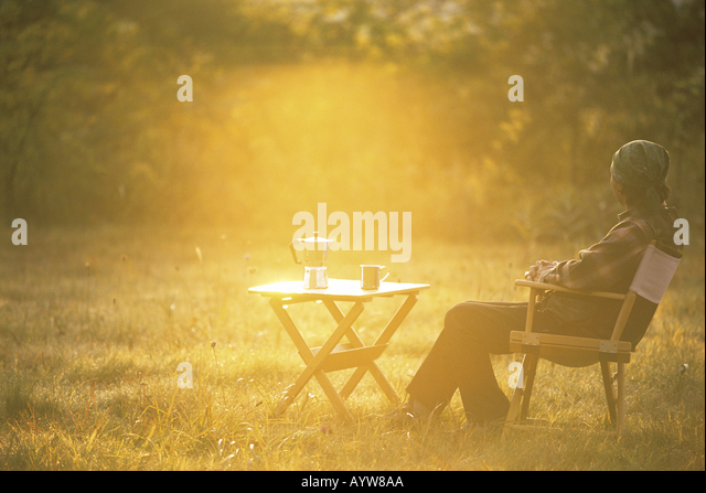 Man with hot coffee sitting on a chair in the garden - Stock-Bilder