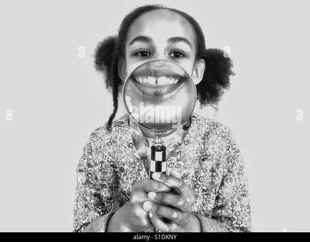 A young girl playing with a magnifying glass. - Stock-Bilder