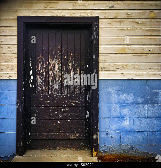 A brown door with peeling paint on a two tone building - Stock Image