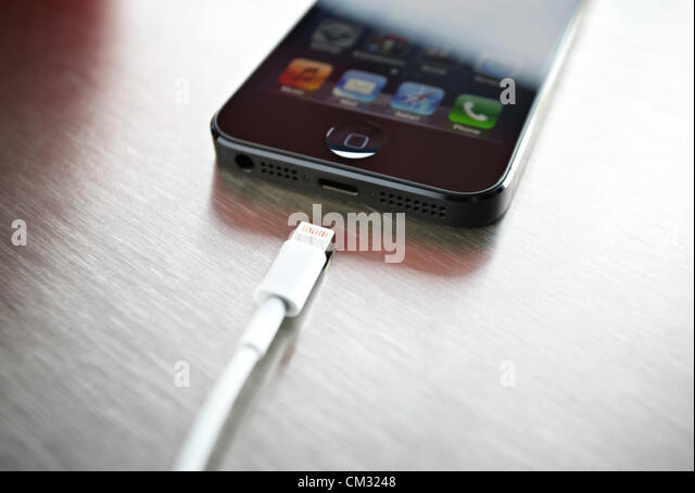 Inside a coffee shop, a newly released, black, Apple iPhone 5 sits face up on a metal countertop next to Apple's - Stock Image