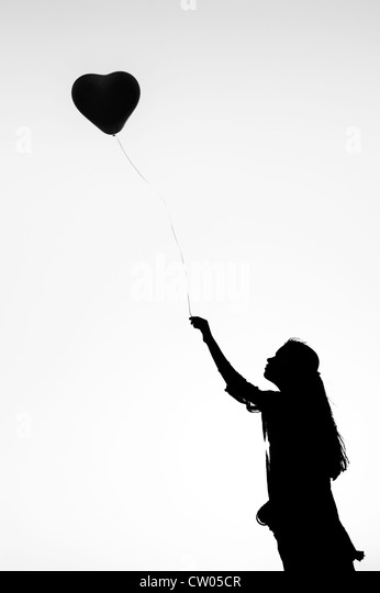 Indian teenage girl holding a heart shaped balloon. Silhouette. Monochrome - Stock Image