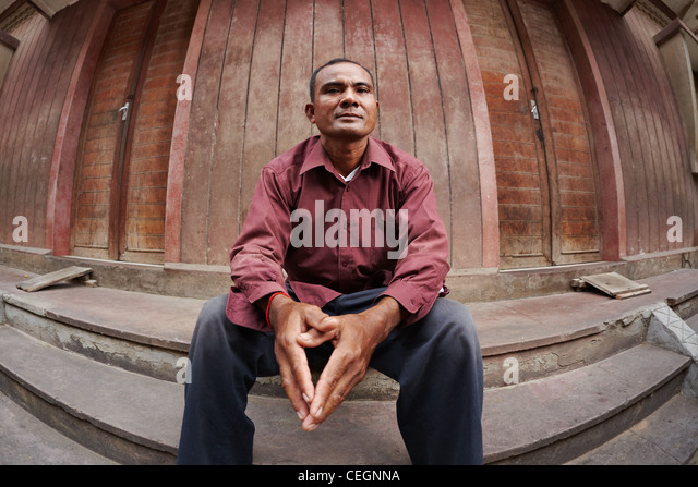 Portrait of mid adult poor asian man with hands joined, looking at camera. Fisheye shot - Stock Image