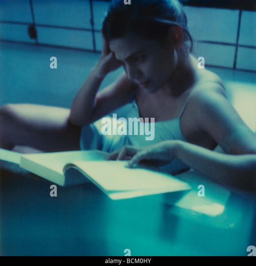 Woman sitting in bathtub, reading - Stock Image