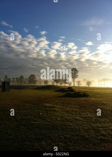 Early morning rural scene with cloudy sky and rugby goalposts - Stock Image