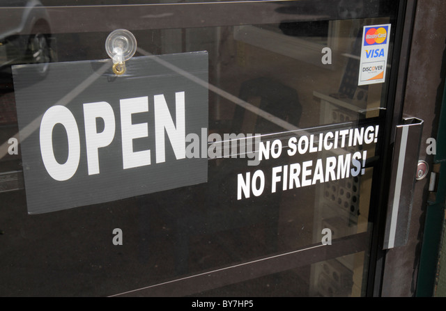 Nashville Tennessee door business entrance warning sign open visa no soliciting no firearms - Stock Image