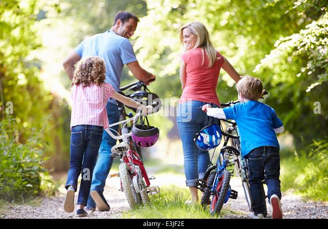 Family Pushing Bikes Along Country Track - Stock Image