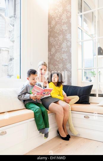 Full length of children listening mother reading story book in living room - Stock Image