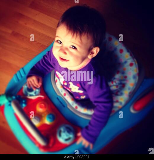 Baby girl in walker, blurred shot from above - Stock-Bilder
