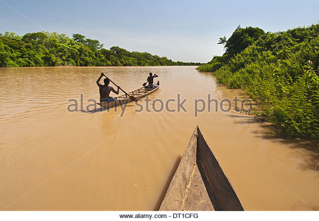 Black Volta river Ghana Men paddling canoe upstream Black Voltriver Ghana - Stock Image