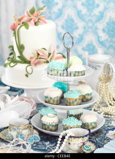 Still life photo of a luxurious tea party with sweets, jewellery and accessories - Stock Image