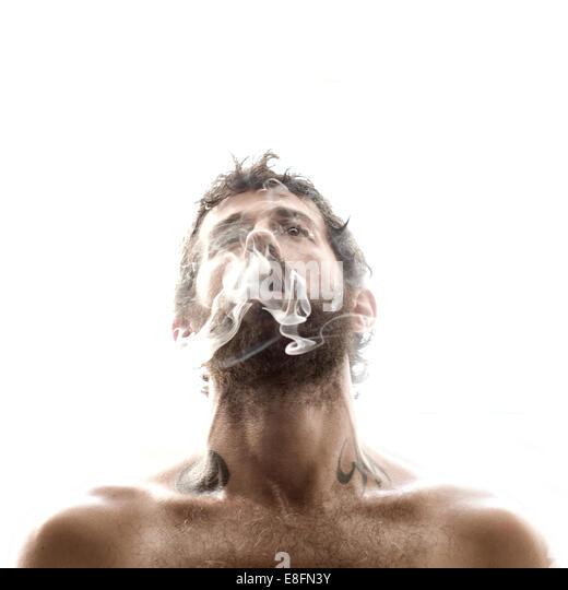 Man exhaling smoke - Stock-Bilder