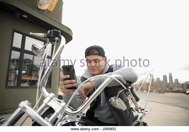 Male biker texting with cell phone on motorcycle in parking lot - Stock-Bilder
