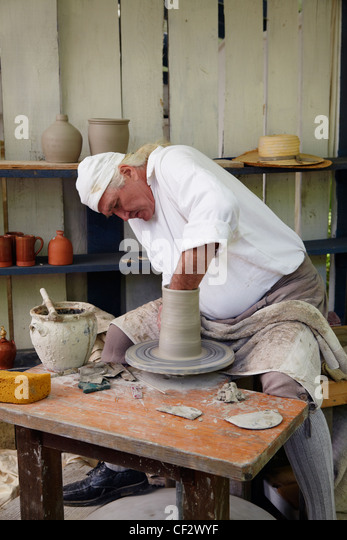 A potter throws a pot at the Claude Moore Colonial Farm market fair, McLean, Virginia, where it is always 1771. - Stock Image