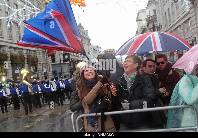 London,UK,1st January 2014,Strong winds blew umbrellas inside out at the London's New Year's Day Parade - Stock Image
