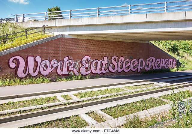 Graffitti saying work, eat, sleep, repeat on a bridge over the guided busway near Longstanton in Cambridgeshire - Stock Image