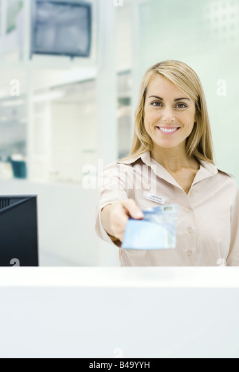Travel agent holding out ticket, smiling at camera, personal perspective - Stock Image