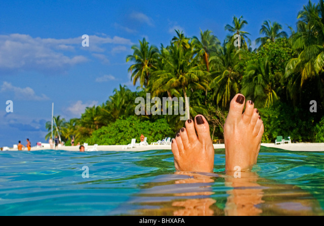 Womens feet , Palm trees at the beach of Biyadhoo Island , Indian Ocean , South Male Atoll , Maldives - Stock Image