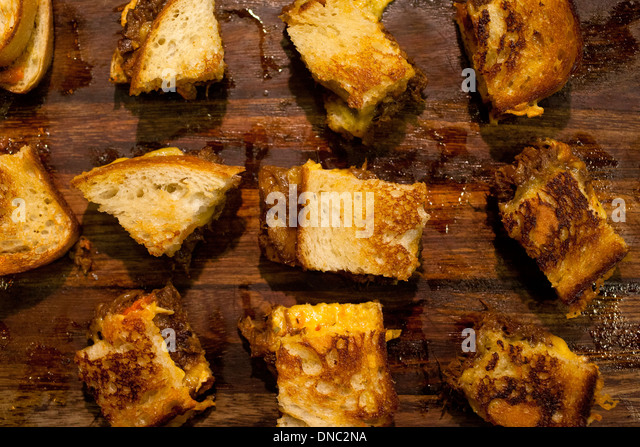 Quartered grilled cheese sandwiches on wood cutting bord - Stock Image