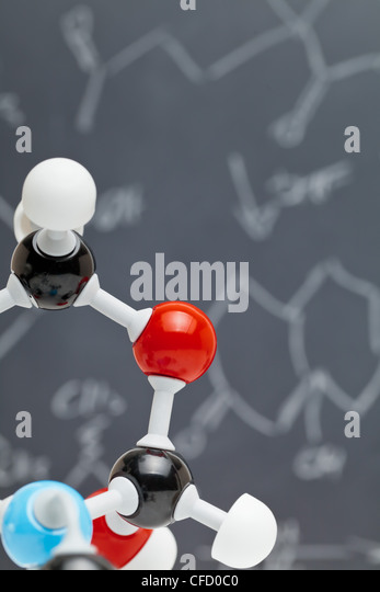 Molecule model with formulas on blackboard in the background - Stock Image