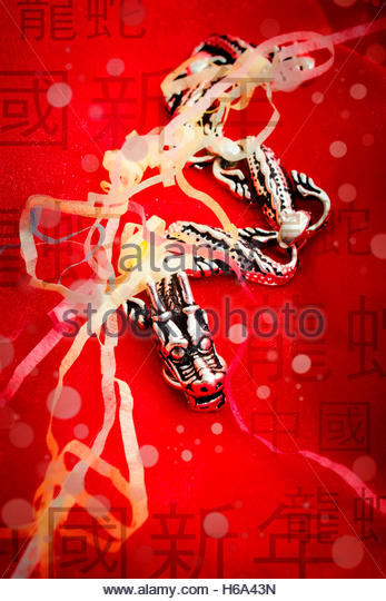 Chinese new year with a silver serpent dragon amongst a celebration of festival confetti - Stock Image