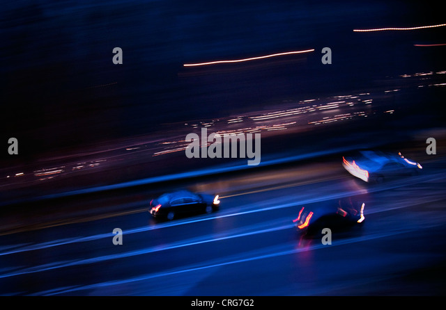 Cars speed down the parkway at night. - Stock Image