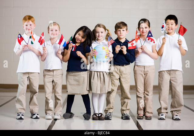 school children waving flags of different countries - Stock Image