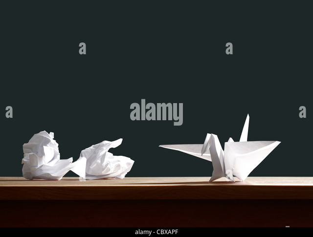 Crumpled paper and origami bird on desk - Stock Image