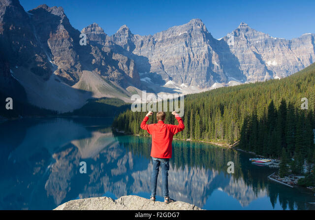 Tourist with open arms on look-out point looking over Moraine Lake in the Valley of the Ten Peaks, Banff NP Alberta, - Stock Image