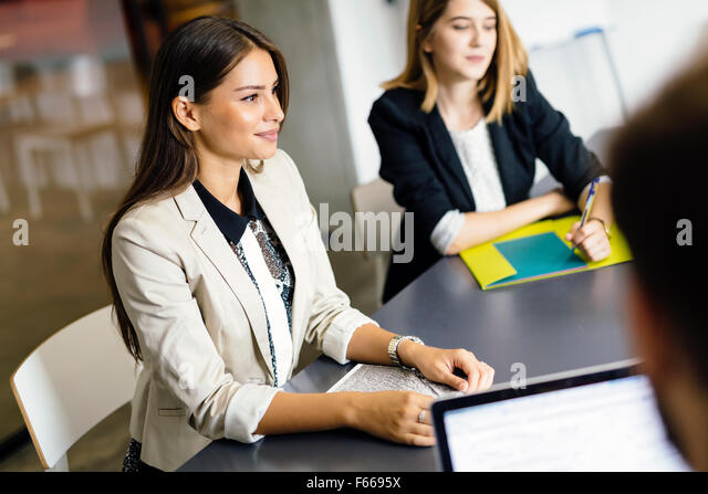 Beautiful businesswoman working in office and smiling - Stock Image