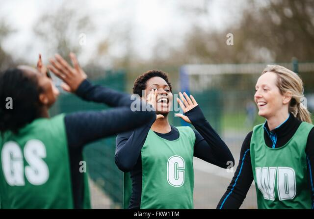 Adult female netball team celebrating win on netball court - Stock Image