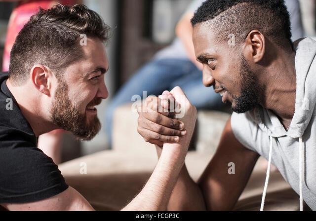 Friends together having a good time arm wrestling - Stock Image