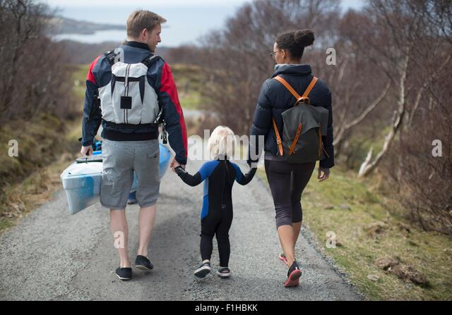 Family walking on country road holding hands, rear view - Stock-Bilder