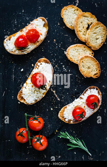 Toast crostini bruschetta with fresh white cheese ricotta, roasted cherry tomatoes and garlic olive oil. Top view - Stock Image