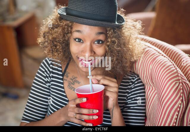 Portrait of young woman wearing fedora and drinking soft drink - Stock Image