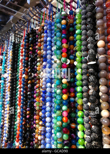 Strands of beads of semi precious stones at a bead shop. - Stock Image