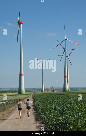 Wind farm and joggers, Germany, Europe - Stock Image