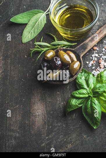 Green and black Mediterranean olives with fresh herbs - Stock Image