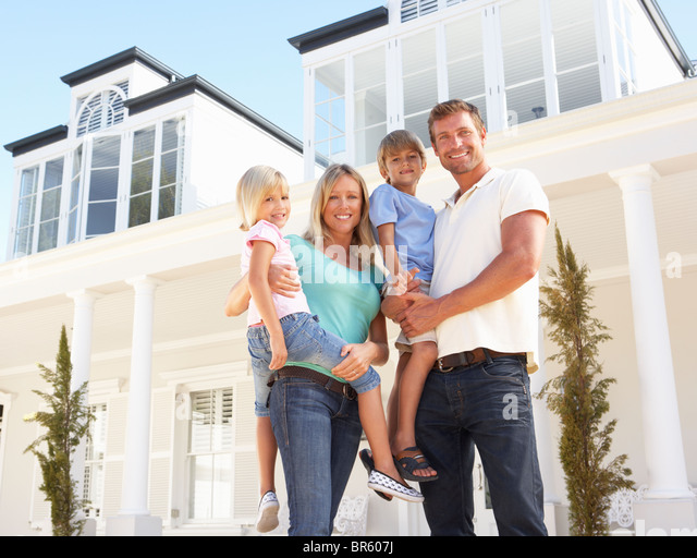 Young Family Standing Outside Dream Home - Stock Image