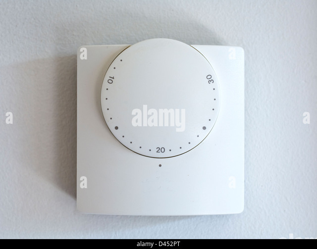 A central heating wall thermostat set at 20 degrees centigrade - Stock Image