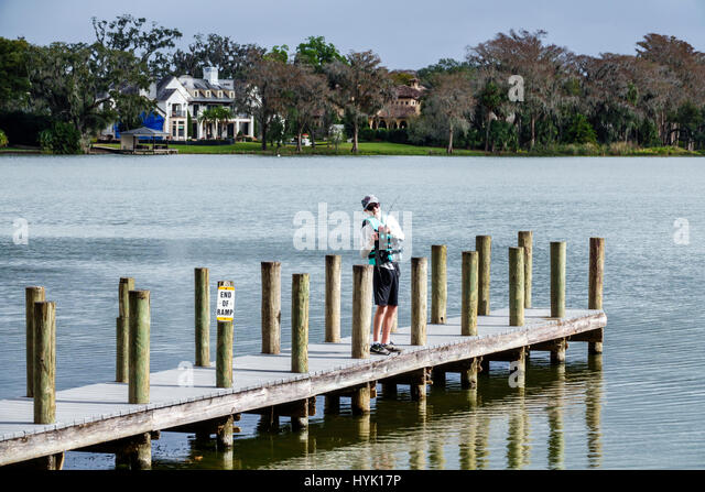 Winter Park Orlando Florida Lake Virginia Dinky Dock Park dock boy fishing scenic calm water - Stock Image