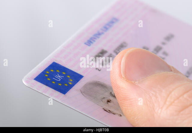 Holding out a driving license - Stock Image