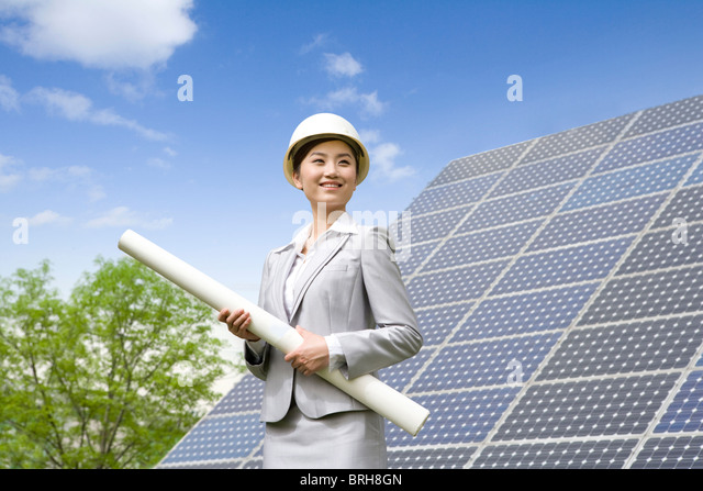 Portrait of an engineer in front of solar panels - Stock Image