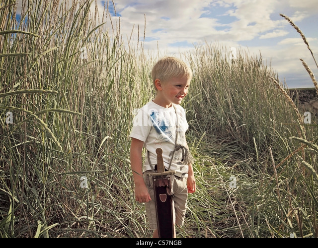 Boy playing with sword in wheat field - Stock Image