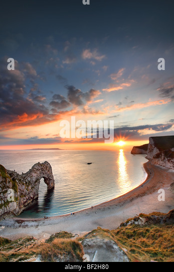 Durdle Door at sunset with people on beach, Dorset. - Stock Image
