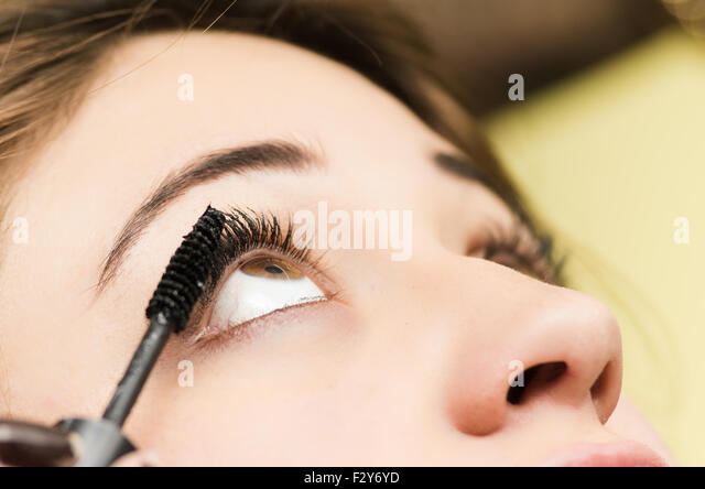 Closeup headshot brunette getting makeup treatment by professional stylist applying mascara on eyelashes - Stock Image