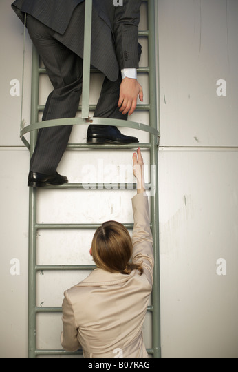 Businessman on fire escape, reaching down to businesswoman's hand below - Stock Image