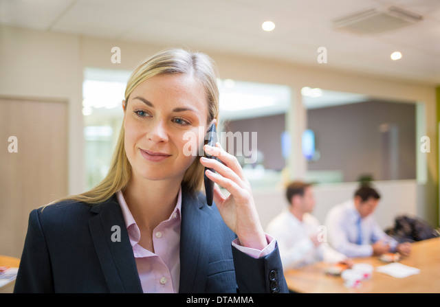 Businesswoman telephoning in her office - Stock Image