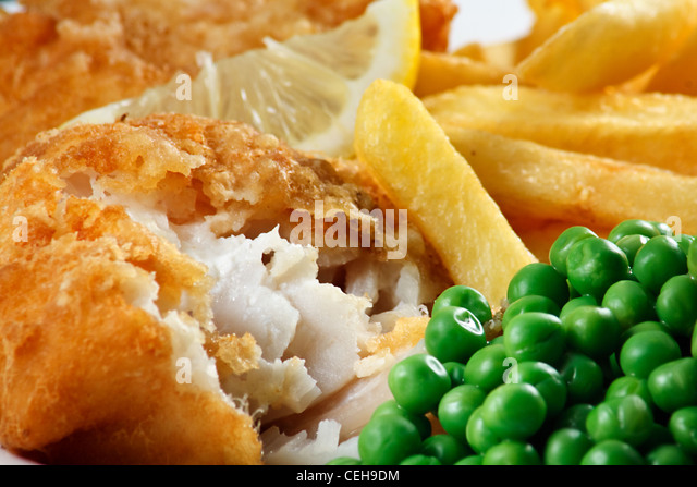 Close up of fish and chips with peas and a slice of lemon. A traditional British Seaside Dish - Stock-Bilder