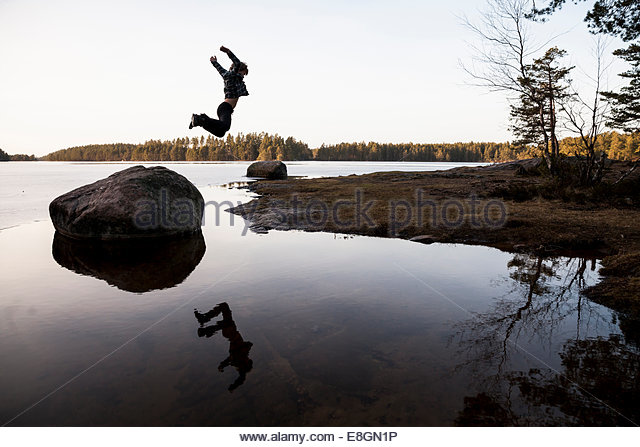 Full length of boy jumping off stone over water - Stock Image